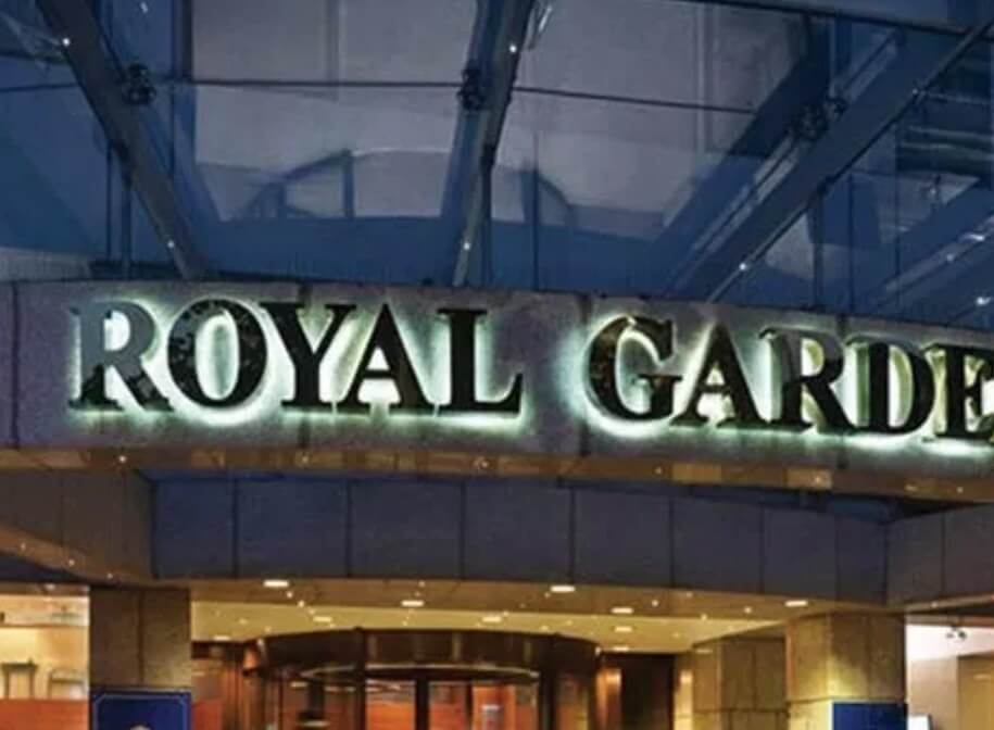 the royal garden sign lit up during the night